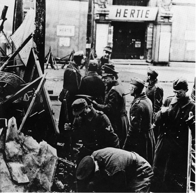 Under Wehrmacht supervision, Volkssturm troops set up a makeshift barricade in a Berlin street in hopes it would stop the advancing Red Army. The VS men shown here wear military uniforms, unlike many others who were simply provided an armband worn over their civilian clothes.