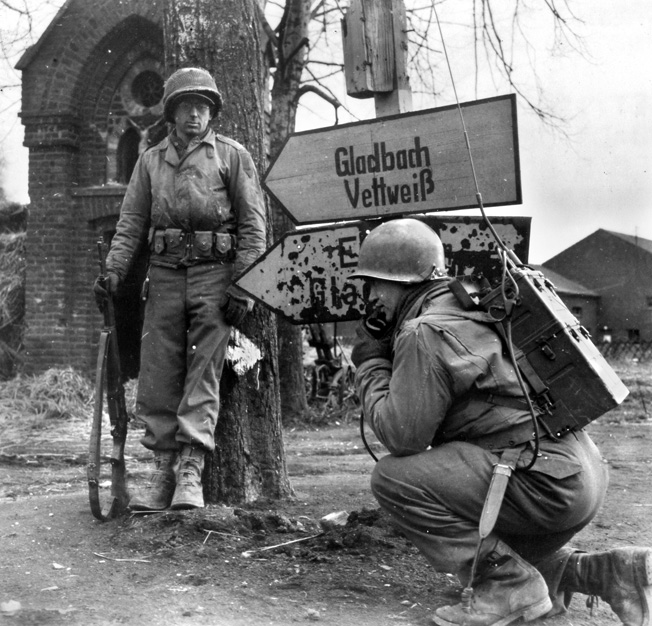 Men of the 1st U.S. Army use a Walkie-Talkie at a crossroads inside Germany. The new SCR-300 radio allowed for better communication over longer distances, allowing frontline troops to speak to their headquarters several miles to the rear.