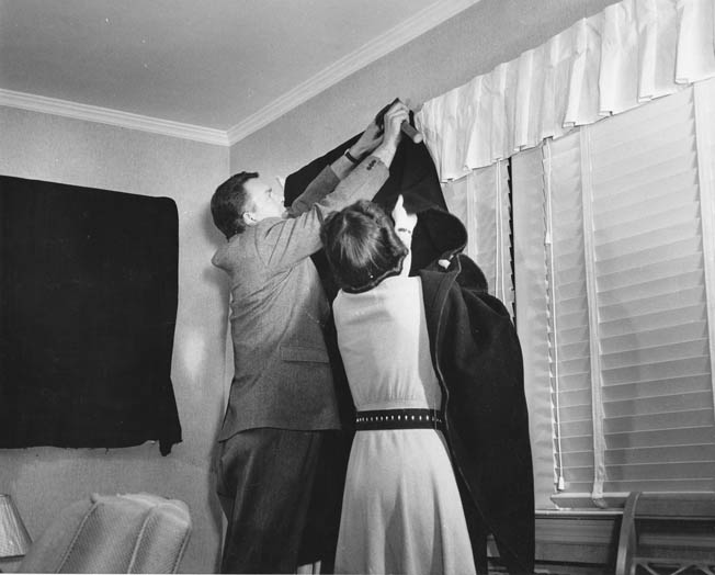 A U.S. government publicity photo from the Office of Emergency Management shows a family installing blackout curtains.