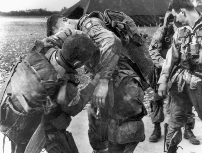 82nd Airborne Division paratroopers strap on their gear at an airfield in England before the Normandy jump.