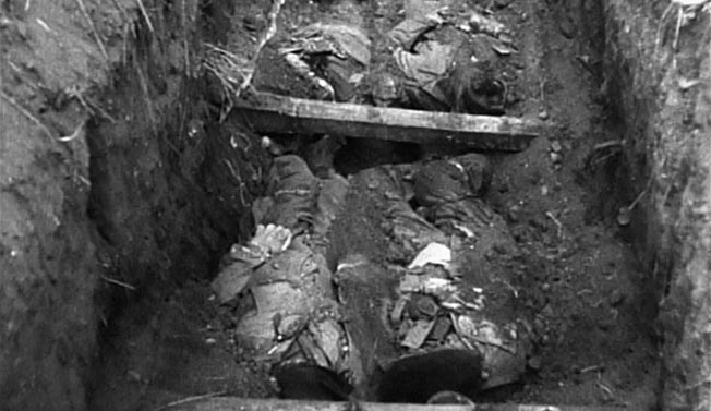 The bodies of Heck, Hitztaler, Kling, McElhaney, Tillman, Watson, and Werner have just been uncovered in this frame from Sergeant Thomas J. Maloney's motion picture footage of the U.S. First Army Inspector General's investigation at Hémevez on June 22, 1944.