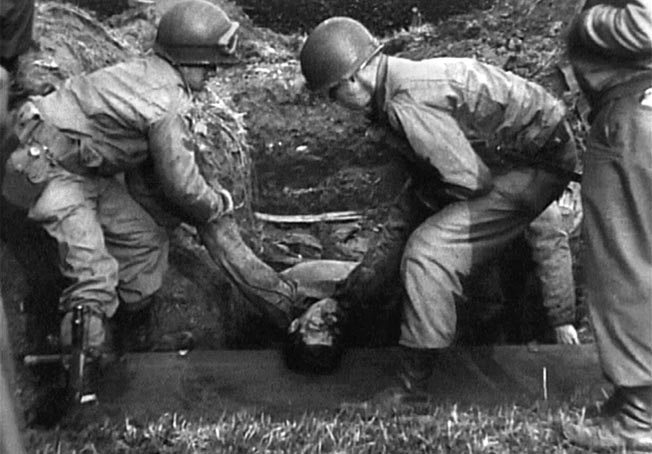 The body of a murdered paratrooper is removed from the mass grave at Hémevez, June 22, 1944. The villagers buried the Americans as carefully as they could, believing they would be reinterred after American forces arrived in the area.