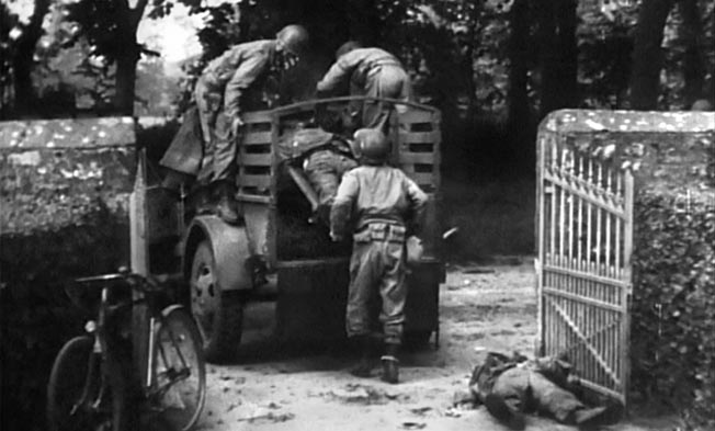 The bodies of the eight slain paratroopers are placed in a weapons carrier and trailer belonging to the 603rd Quartermaster Graves Registration Company for the 10-mile journey to the village of Ste-Mère-Église, where they were buried in a temporary U.S. military cemetery.