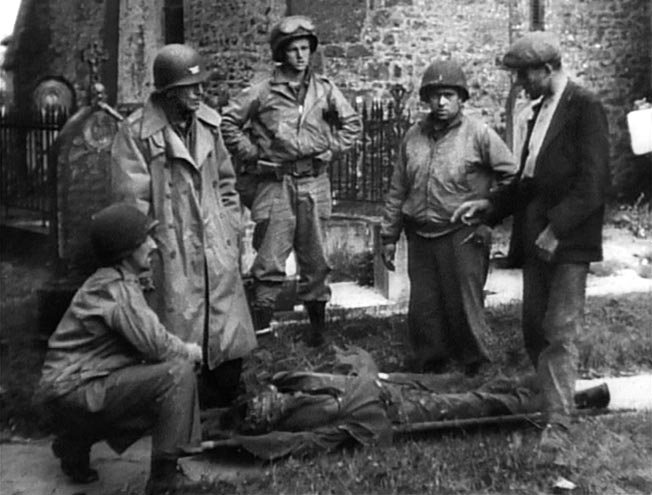 Pierre Renault (right), who saw the paratroopers being taken into the woods to be killed, talks with Colonel Rosser L. Hunter (standing, left), June 22, 1944. A portion of the church at Hémevez is visible behind the group.