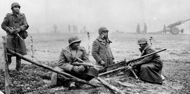 G3C42G An American field artillery unit dig in along a Belgian road, in position to hold ground against the German counter-offensive in the Ardennes area of Belgium which became known as the Battle of the Bulge. From left to right, Private G.F.Morris of New York