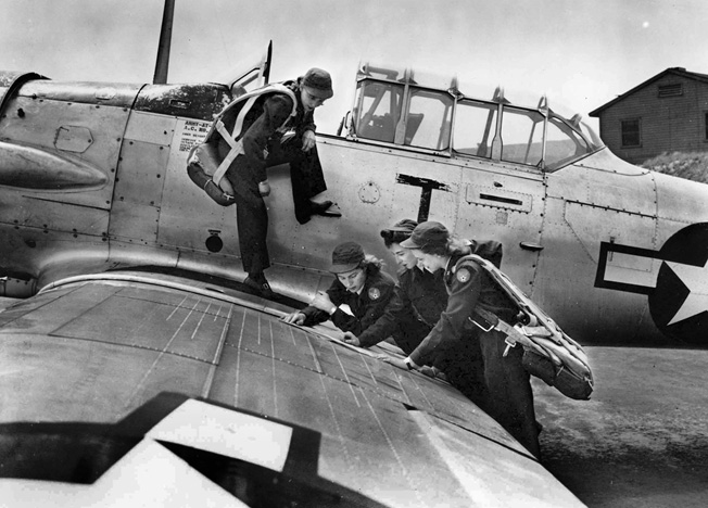 Four WASPs view an aerial chart on the wing of an AT-6 trainer.