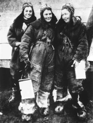 Three Soviet women of the 46th Guards Night Bomber Aviation Regiment in their oversized leather flying uniforms. The woman in the middle has a pistol tucked into her belt.