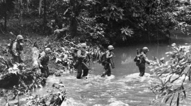 Marine Raiders cross a stream during the advance on Enogai Point, August 1943. Extreme heat, humidity, disease, and a tough, well-camouflaged enemy took a heavy toll on American troops.