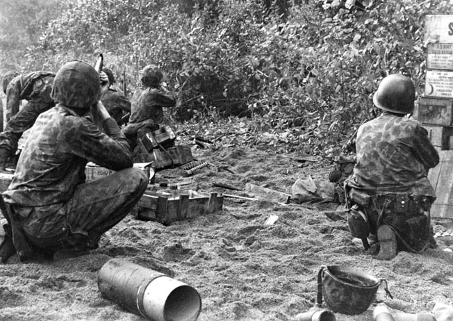 U.S. Marines fire at Japanese snipers hidden in the dense foliage at one of the landing beaches. Enemy opposition was heavier than U.S. planners expected.