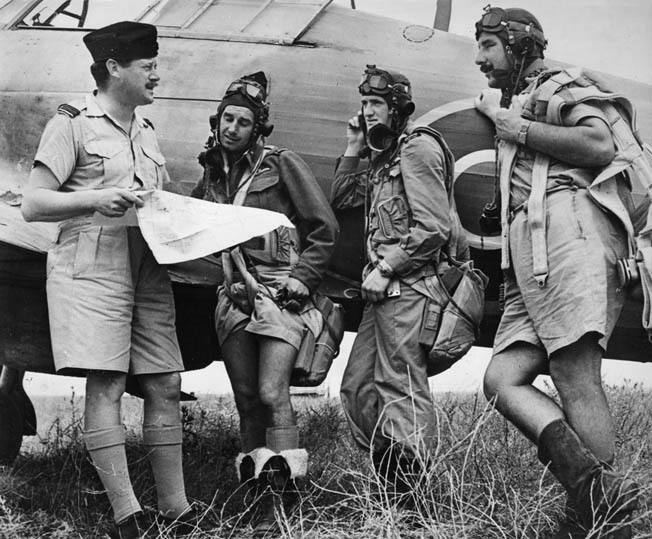 An RNZAF officer briefs a group of pilots standing beside what is possibly a Curtis P-40 Kittyhawk Mk IV fighter.