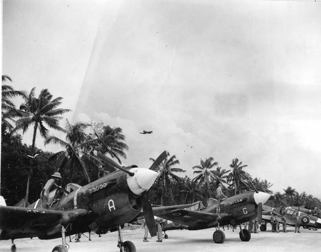 While a Vought F4U Corsair streaks overhead, New Zealand P-40s, provided by the United States, are serviced after returning from a strike on Rabaul in December 1943. The RNZAF got good service out of the obsolescent P-40s.