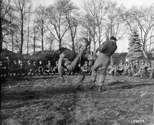 A British Commando demonstrates fighting tactics to a group of Rangers during training at Achnacarry, Scotland. Colonel William O. Darby modeled his Ranger battalions after the tough British Commando units.