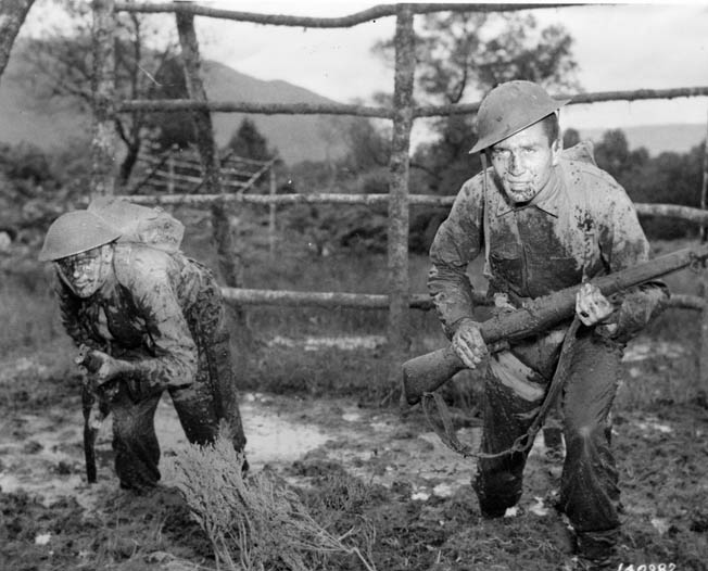 Wearing World War I-style helmets and carrying British Lee-Enfield .303 rifles, two muddy U.S. Rangers undergo obstacle-course training in Scotland prior to making a failed invasion at Dieppe, France, in August 1942.