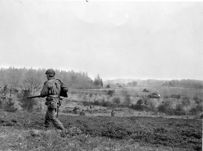U.S. infantrymen and a platoon of Sherman tanks from CCB, 10th Armored Division, advance toward enemy positions hidden in a forest in Germany.