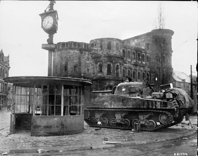 A Sherman tank from the 10th Armored Division moves through Trier, near the Saar River north of Saarburg, a week after linking up with the 2nd Ranger Battalion. Behind the tank is Trier's famous landmark, the ancient Roman gate known as the Porta Negra.