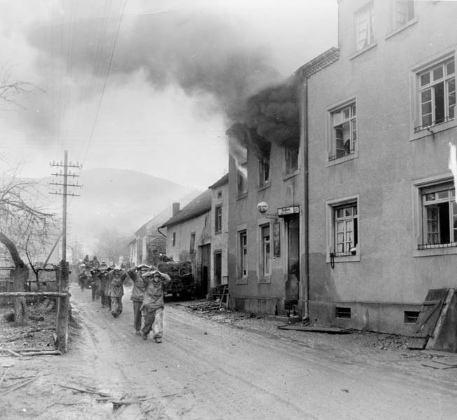 German prisoners are marched through Irsch, east of Saarburg, on February 27. Lt. Col. Richard P. Sullivan's 5th Ranger Battalion captured 328 enemy soldiers during their operation at Zerf.