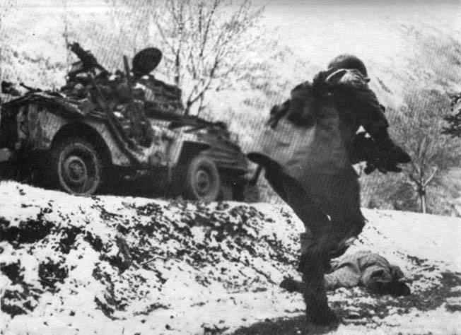 A 45th Division soldier rushes past a casualty below a road occupied by a jeep and Sherman tank near Reipertswiller, January 15, 1945.