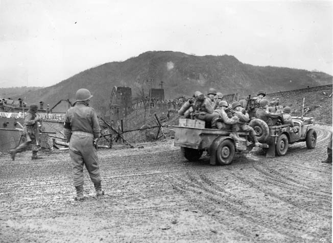 A jeep full of American soldiers pulls a trailer that is also filled to capacity with GIs as it nears the western approach to the Ludendorff Railroad Bridge at Remagen.