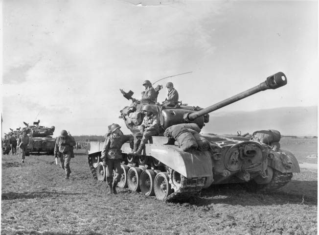 In March 1945, the crew of an American M26 Pershing heavy tank takes a break somewhere in western Germany. The Pershing, with its 90mm main gun, was developed as a match for the heavy German Tiger tank. While few of them reached the battlefields of Western Europe before the end of the war, a platoon of M26 Pershings from the 14th Tank Battalion fought at Remagen.