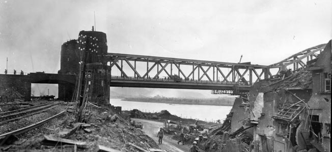 The ruins of the town of Remagen around them, American soldiers go about their business on March 11, 1945. The Remagen Bridge remained virtually intact for 10 days after its capture, allowing the Americans to move men, tanks, and supplies to their lodgment on the eastern bank of the Rhine River.
