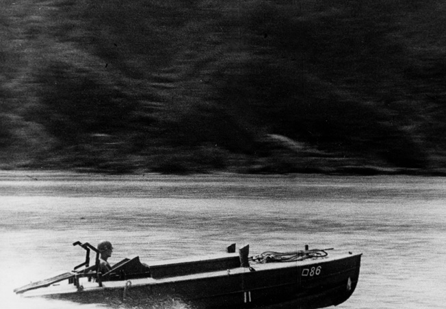 An American officer takes a spin in one of the captured suicide boats. The speed of the boat has lifted the bow out of the water.