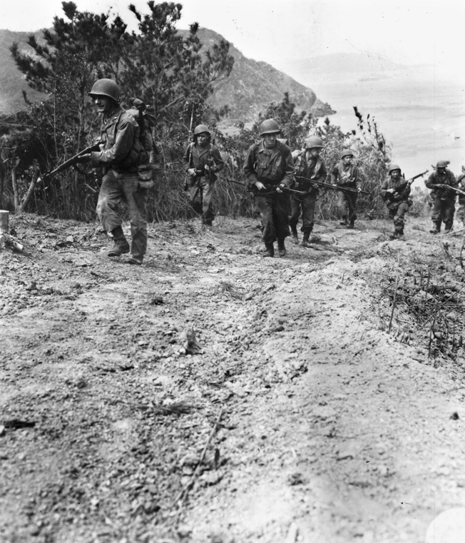 An advance patrol of the 77th Infantry Division moves cautiously up a trail on Takashiki Shima, scouting an advance route for the main body that later overran the island.