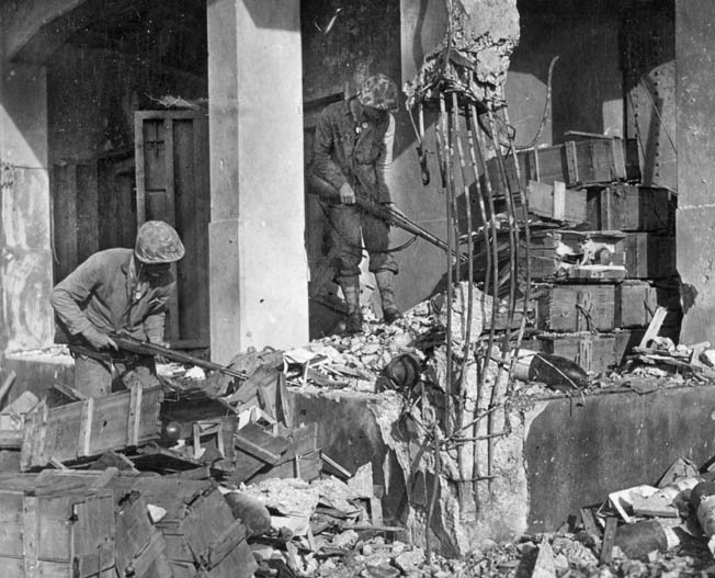 Cautious with every step, these Marines pick their way through the ruins of a building previously used by the Japanese on Roi-Namur to store ammunition.