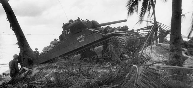 Having taken cover on the beach at Roi, American Marines With a couple of Marines watching intently, an M4 Sherman medium tank moves across the sandy berm adjacent to the beach at Namur.
