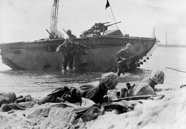 Marines leap over the side of their amphibious Amtrac landing craft during operations in the Marshall Islands. Instead of attacking the strong defenses of islands in the outer Marshalls, the Marines struck at Roi-Namur while veteran Army troops attacked Kwajalein.