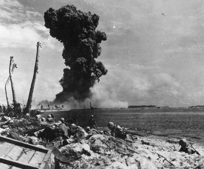Having taken cover on the beach at Roi, American Marines look across the lagoon toward Namur as a huge explosion destroys a Japanese bunker. Marines on the adjacent island had placed a satchel charge to destroy the bunker, and its demolition ignited an ammunition storage area with spectacular results.