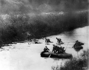 German soldiers in rubber rafts paddle across the Meuse River as others crawl across a footbridge to avoid enemy fire.