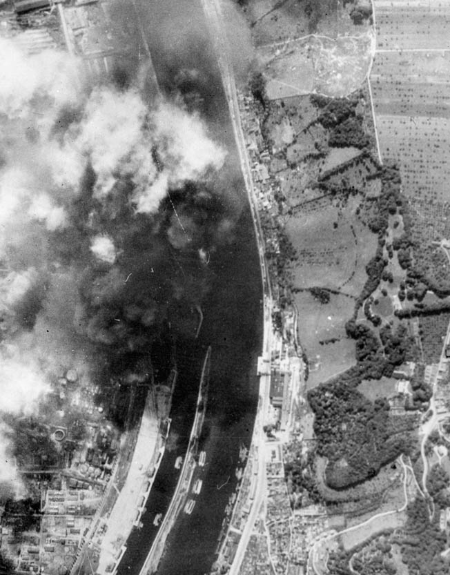 Smoke pours from a Rouen oil depot during a raid by the U.S. Eighth Air Force in August 1944.