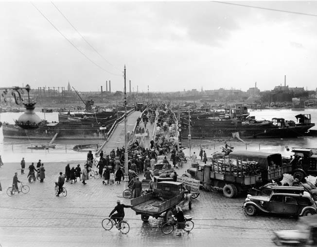 Civilians use a temporary bridge in Rouen. The bridge includes a barge that can be moved to allow for river traffic.