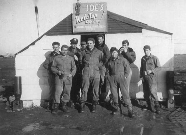 """Crew members grab refreshments at """"Joe's Red Top Drive-In"""" between 767th Headquarters and the flight line at Torretta Field Air Base at Cerignola, Italy. Rowe (fourth from right) said, """"'Joe' was a young Red Cross lady who always had fresh coffee and doughnuts any time we came by. I don't know when she slept."""""""
