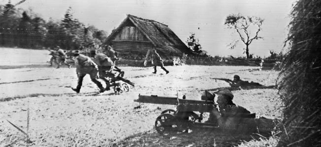 Advancing near the border of East Prussia, Red Army soldiers launch a probing attack against nearby German positions. The infantry support machine guns were often mounted on wheeled carriages, and these are prominently visible as the troops rush across a farmyard in September 1944.