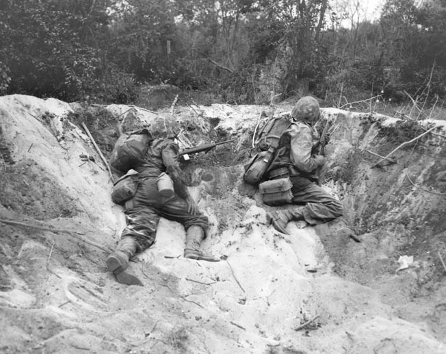 Two Marines take cover in a shellhole on Saipan.