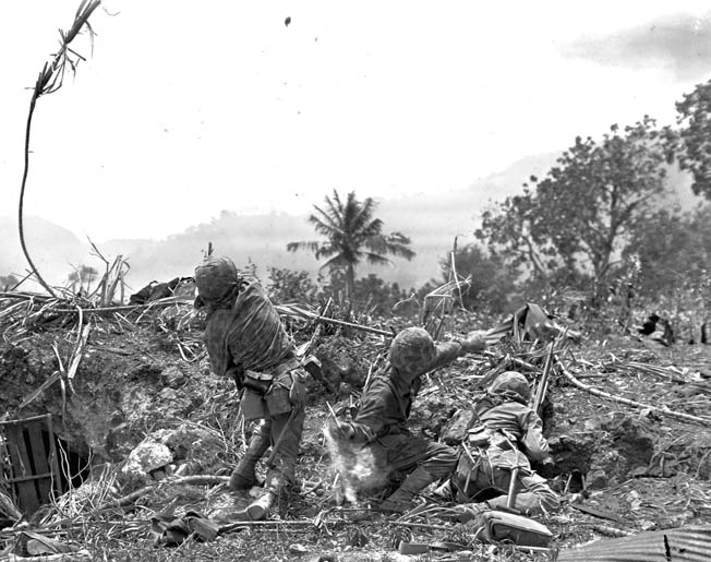 From the cover of a shell hole, U.S. Marines throw grenades across the shattered landscape of Saipan toward Japanese positions. The stubborn Japanese defense of Saipan resulted in a bloody 39-day campaign to capture the island, and the differing combat doctrines of Marine and Army troops compounded the discord among the highest echelons of the American command.