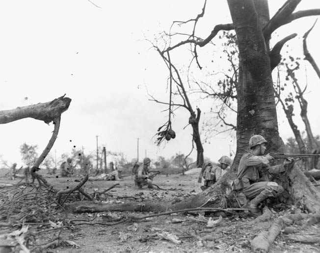 Marines keep low while moving against Japanese positions in the city of Garapan. More than 3,000 American servicemen were killed during the battle.