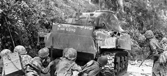 "Marines advance behind a M4A2 Sherman tank (dubbed ""King Kong"") of the 4th Tank Battalion while cleaning out the northern end of the island. The Japanese were well dug in and prepared to defend to the last man."