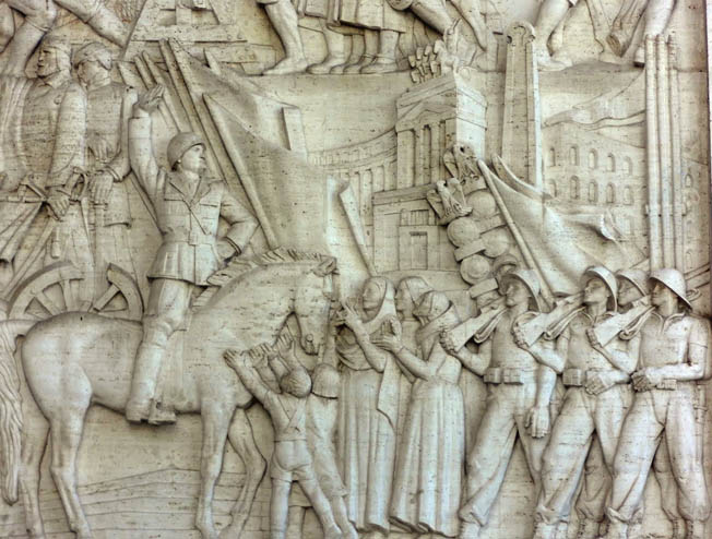 A bas relief on walls of the Palazzo degli Uffici dell'Ente Autonomo shows Il Duce being hailed by Italian civilians and soldiers of the modern Roman Empire.