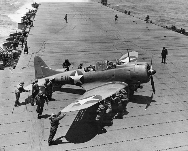 Flight-deck crew on the USS Hornet pushes an SBD of Bombing Squadron VB-8 into position for takeoff during the Battle of Midway, June 2, 1942.