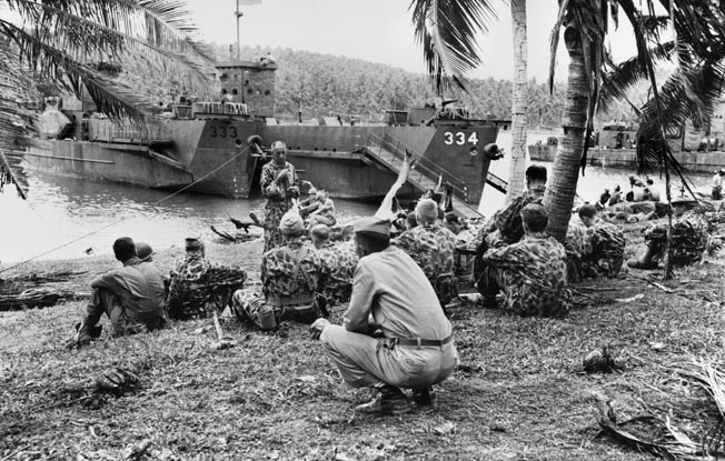 Lieutenant Colonel Lester Brown (standing) briefs officers of the 103rd Regiment, 43rd Infantry Division, dressed in camouflage-pattern uniforms, prior to boarding several LCIs (Landing Craft, Infantry) in the Russell Islands for transport to Rendova, June 1943.
