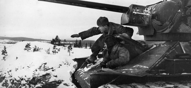 In this obviously posed photo, Soviet tank crewmen scan the horizon for enemy troop movements during their Ukraine offensive undertaken in the winter of 1943. One of the soldiers gestures as though he has located something of interest—probably at the suggestion of the photographer.