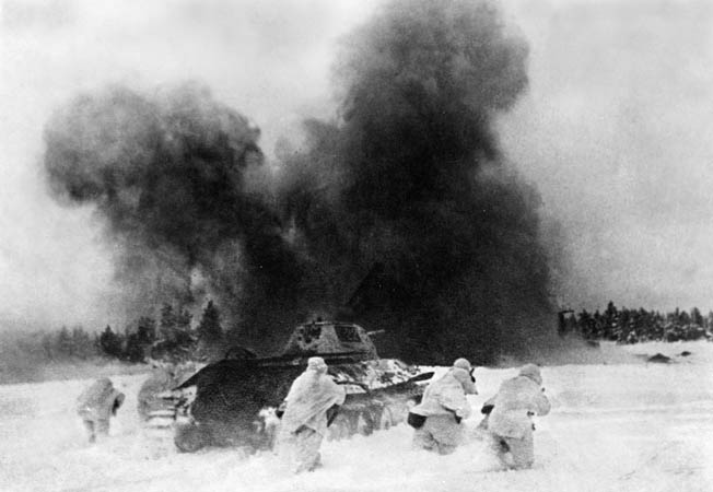 Taking cover behind a T-34 tank, Red Army infantrymen advance through knee-deep snow toward a German position.