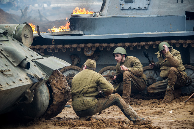 Russian reenactors take cover behind a T-34 tank (left) and a 'knocked out' mock Panzer (right) as they storm the model Reichstag at Patriot Park. Photo Credit: Ministry of Defense of the Russian Federation.