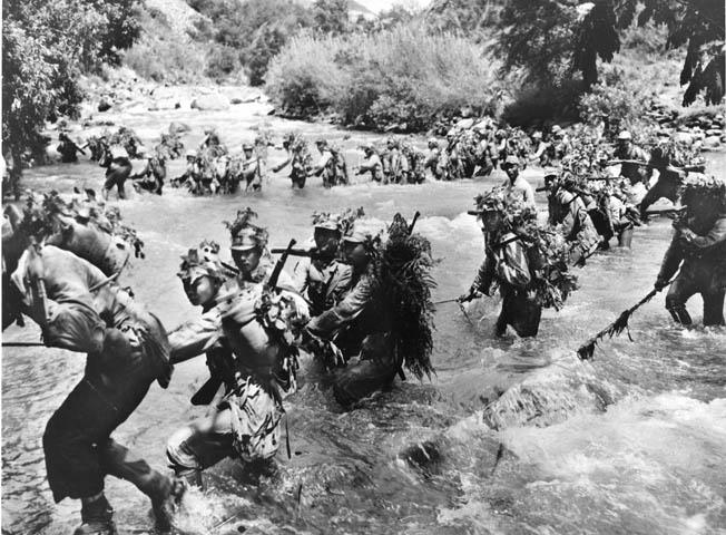 Chinese troops, camouflaged with foliage, ford a swift-flowing river during the advance to the Salween.