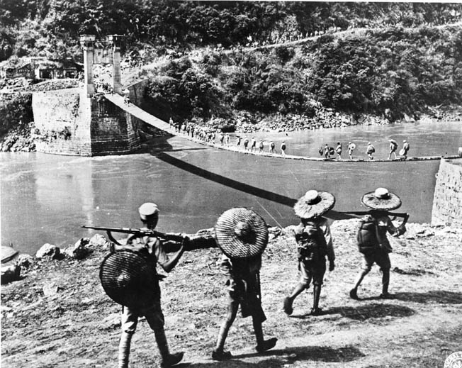 Chinese troops carrying weapons and supplies cross the Salween over the temporary Huitong Bridge, July 1944. While Allied forces advanced on Myitkyina, Chinese troops crossed the Salween from the east. The two forces met at Tengchung in September 1944, establishing the first thin hold in northern Burma.