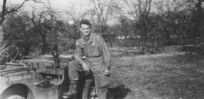 """Captain C. Lenton """"Charlie"""" Sartain, one of the heroes of Finger Ridge, photographed with his jeep, Indiana Anne, November 1944."""