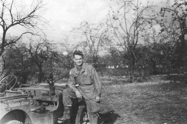 "Captain C. Lenton ""Charlie"" Sartain, one of the heroes of Finger Ridge, photographed with his jeep, Indiana Anne, November 1944."