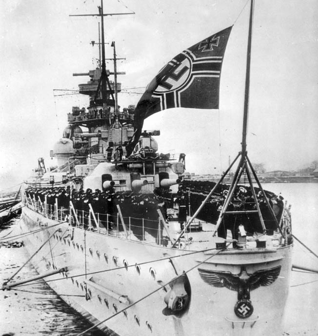 This photograph records one of the proudest moments in the star-crossed career of the battlecruiser Scharnhorst, the commissioning ceremony for the new warship in the harbor at Wilhelmshaven, Germany, on January 7, 1939.